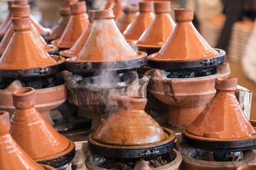 Preparing food in tajin traditional dish in Morocco - meat and vegetable in a ceramic tajine.