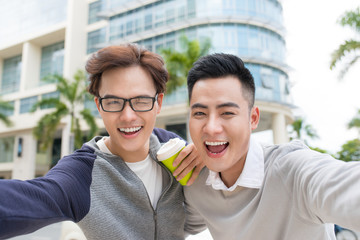 Two Vietnamese men traveler taking selfie in foreign city
