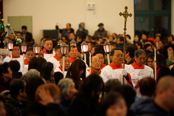 Faithful attend a Christmas Eve Mass at a Catholic church in Shanghai