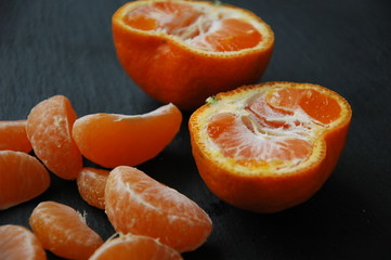 A few tangerines close-up on a black background.