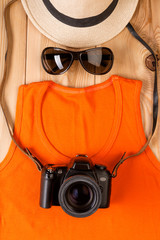 the image of a tourist photographer from clothes and accessories on wooden boards view from above