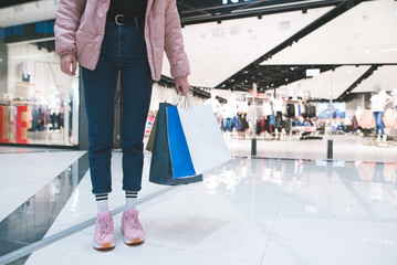 Stylish girl with shopping bags in her hand against the backdrop of a clothing store in the mall. Shopping concept.
