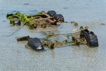 Mit Moos und Algen bewachsenes Wrack eines Fahrgestells  im flachen Wasser in Strandnähe