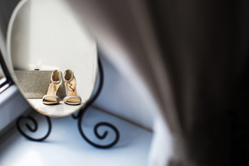 Reflection of a wedding shoes and silver purse