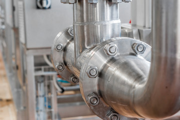 Connection of stainless steel pipes with bolts. Brilliant surfaces.