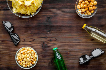 Cinema food. Crisp, popcorn, rusks near glasses on dark wooden background top view copyspace