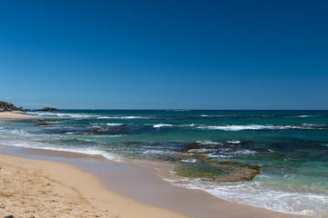 Brandung am Strand mit Stein-Plateau im seichten Wasser, welches von Wellen umspült wird