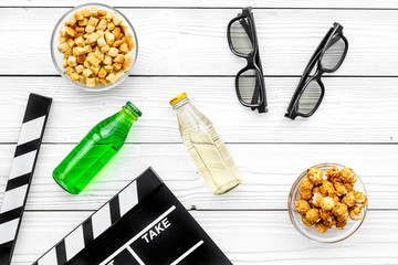Popcorn, rusks and drink for watching film. Clapperboard and glasses on white wooden background top view