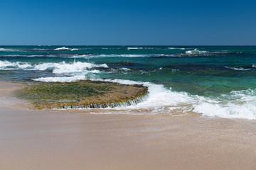 Nahaufnahme der Brandung am Strand mit Stein-Plateau im seichten Wasser, welches von Wellen umspült wird