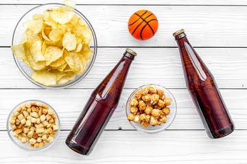 Snacks for watching sport matches and games on TV. Crisps, popcorn, rusks near drink and ball on white wooden background top view