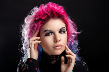 Glamorous portrait of a girl with pink hair and bright makeup on black isolated background close-up