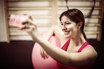 Girl taking a self portrait in gym using phone.