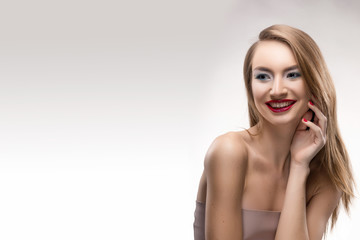 The beautiful blonde red lips smiling girl touches by fingers face and a neck and looks sideways