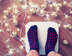 The man got up on white electronic scales after celebration of New Year and Christmas. His hairy feet are dressed in blue socks with red dots. On a wooden floor golden balls and a garland scattered