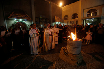 Iraqi Christians pray during a mass on Christmas eve at St.George Chaldean Church in Baghdad