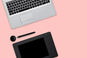 Isolated shot of opened modern laptop computer, tablet for retouching and stylus. Work place of professional retoucher. Pink background. Creativity and job concept.