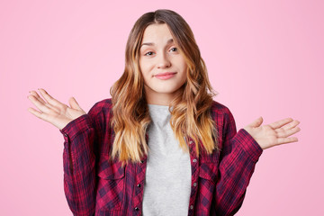 Pretty young woman throws up hands, shows her uncertainty and doubt, dressed in casual checkered shirt, isolated over pink background. Indecisive young female shrugs shoulders in bewilderment
