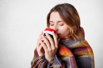 People, cozy atmopshere, season and heating concept. Lovely woman in warm plaid drinks hot tea, warms herself in cold winter, isolated over white background. Female drinks hot coffee at home