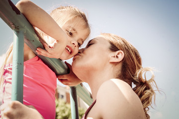 Mother with her daughter share positive emotions. Close up.