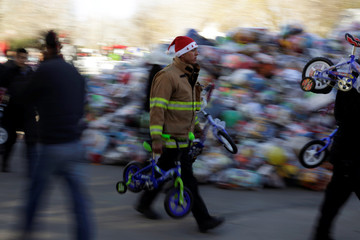 Firefighter carries bicycles during the annual gift-giving event organized by the Fire Department, in which they hand out items donated throughout the year to children in need, in Ciudad Juarez