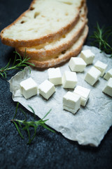 Traditional Greek feta cheese, bread and rosemary on a black background.