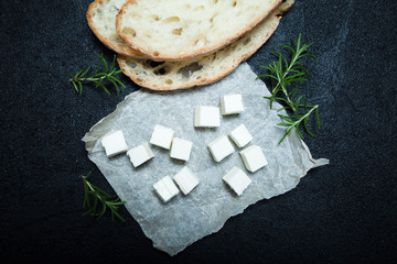 Food for a small snack, traditional feta cheese, bread and rosemary on a black background.