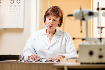 Portrait of a senior woman ophthalmologist in unifrom sitting with different optical devices and eyeglasses during the work in the office