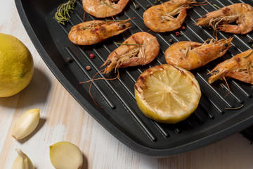 Grilled shrimps on a grill frying pan with lemon, paprika, spices and herbs. Wooden background.