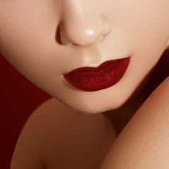 Extreme close up on model applying dark red lipstick. Makeup. Professional fashion retro make-up. dark red lipstick. Wine Lips