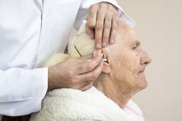 Obraz Czyszczenie uszu starej kobiecie patyczkiem. Higiena i opieka nad osobą starą. - fototapety do salonu