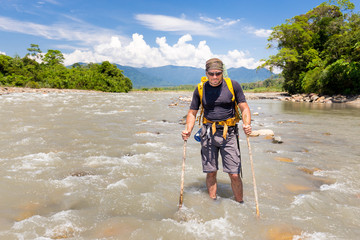 Fototapete - Tough man crossing jungle river stream Quincemil, Peru travel.