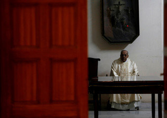 A priest looks on from a room at Saint Joseph's Roman Catholic Church on Christmas eve in Cairo, Egypt