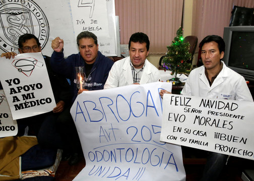 Healthcare employees hold signs during a strike to protest against Bolivia's government new health care policies in La Paz