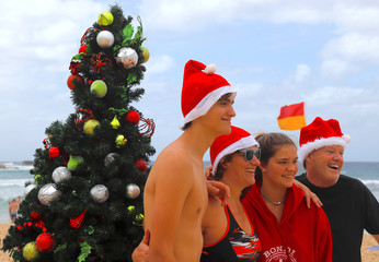 A family stands together in front of a Christmas tree for a photograph as they celebrate Christmas Day on Sydney's Bondi Beach