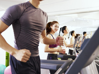 young asian people exercising on treadmill, focus on the girl in the middle