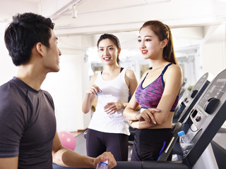 happy asian young people chatting in gym
