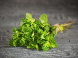 Bunch mint, tied with a rough rope on dark wooden table. The concept of healthy eating.