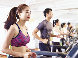 asian young people working out on treadmill