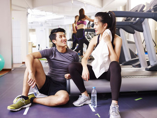 asian young people talking while resting in gym