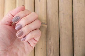 Fashion Brown Manicure Nail. Female's Hand Nails Polish on the Wood Background Great for Any Use.