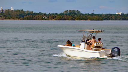 Family outing on the florida intra-coastal waterway in a small sport fishing boat powered by a single outboard engine.