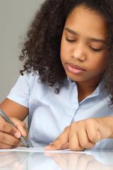 dark-skinned girl draws pencil on paper.