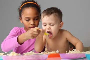 the girl helps the baby to eat spaghetti.