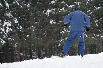 Boy skier in a ski suit and hat standing on snowy slope .