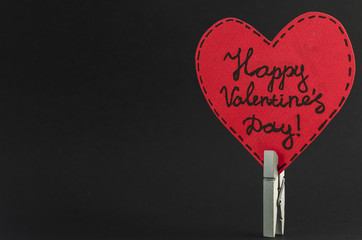 Red heart on the clothespin with the greeting happy Valentines day on dark background