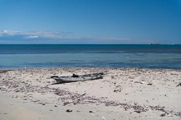 Verlassenes Boot am Strand im Sand im Hintergrund das Meer