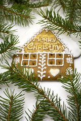 traditional gingerbread house surrounded by fir tree branches