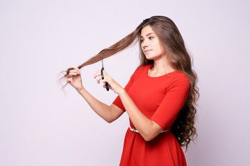 Girl hairdresser. Long hair. Red dress. Black shears