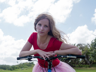 Girl in red dress on a bicycle