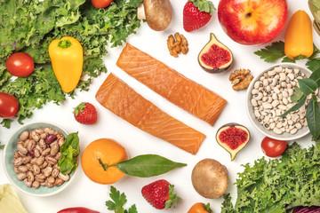 Vibrant fresh food, vegetables, fruits, legumes, fish, mushrooms on white